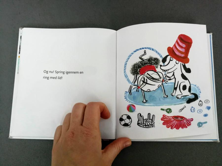 """En side fra bogen """"Lili laver cirkus"""". På siden står der: """"Og nu! Spring igennem en ring med ild i""""."""