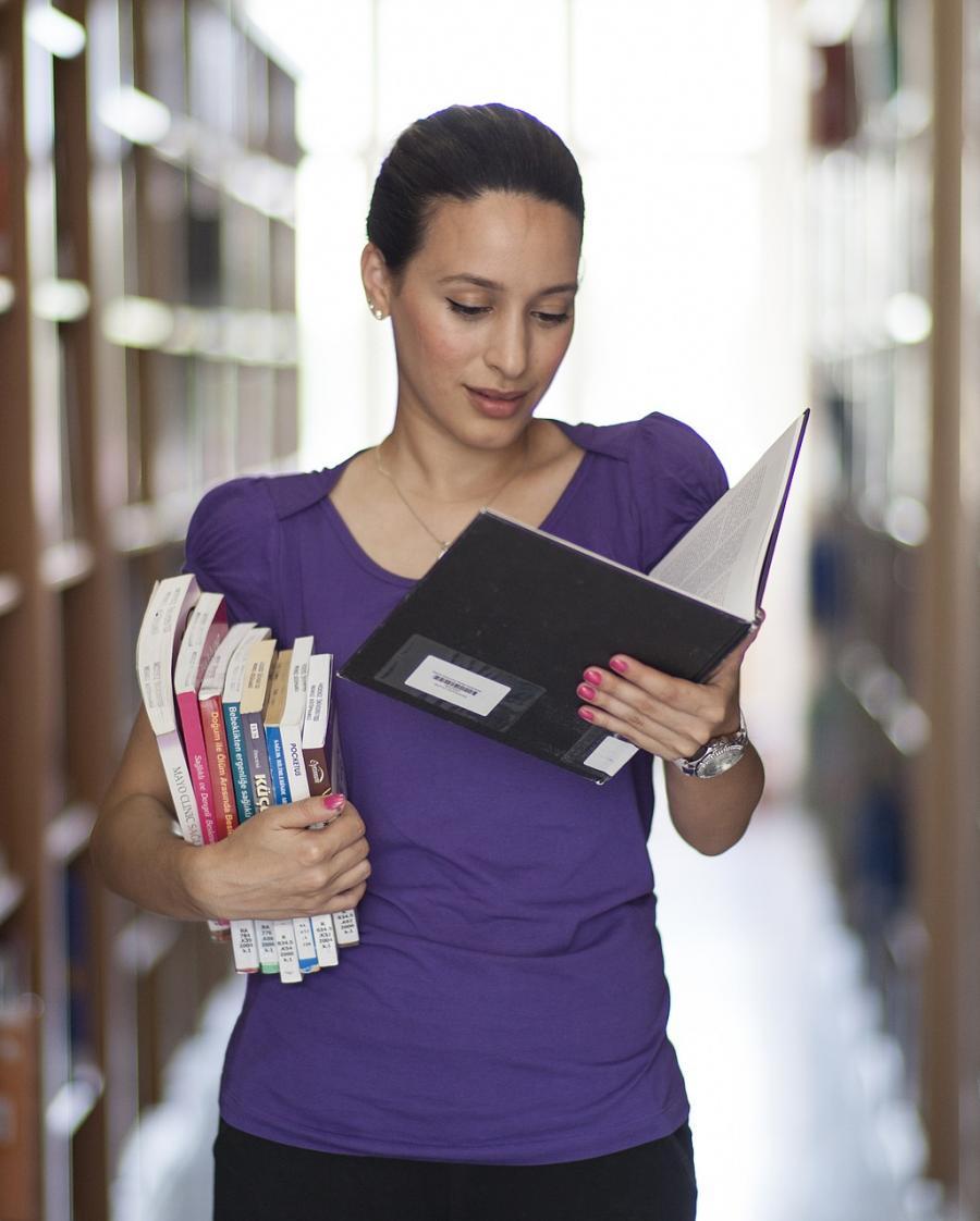 Kvinde med bøger mellem reoler i et bibliotek